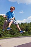 Young boy going airborne with his scooter Royalty Free Stock Photos