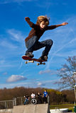 Young boy going airborne with his skateboard. Boy going airborne with his skateboard stock photos