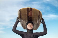 Young boy going surfing. On a cold winters day, rubber hood, booties and gloves Royalty Free Stock Photography