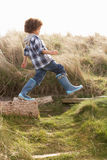 Young Boy Going For Walk In Wellington Boots. In the sun Stock Photos