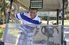 Young boy in golf cart royalty free stock images