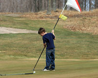 Young Boy with Golf Flag. A young boy putting the golf flag back in the hole on the golf course green Stock Images