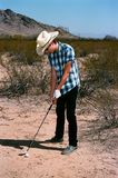Young boy golfing in the desert. Young boy in natural terrain desert golfing royalty free stock images