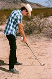 Young boy golfing in the desert. Young boy in natural terrain desert golfing stock photography