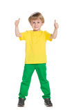 Young boy in green pants. Holds his thumbs up on the white background Royalty Free Stock Image