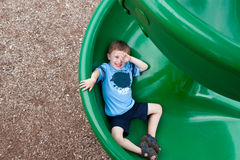 Young Boy on Green Slide. A photo of a young boy sliding down a green circular slide Royalty Free Stock Photo