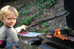 Young boy grilling food. Proud boy cooking hamburgers and hot-dogs outdoors Royalty Free Stock Photos