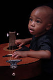 Young boy with guitar. Young African American boy holding an acoustic guitar stock photo
