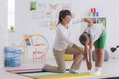 Young boy in gymnastic costume. During posture correction lesson in colorful classroom stock image
