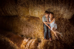 Young boy and gyrl lying in hay.  Outdoor summer portrait of beautiful couple. in hay. Outdoor summer portr Royalty Free Stock Photos