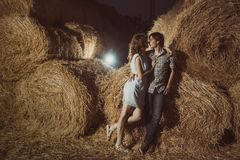 Young boy and gyrl lying in hay.  Outdoor summer portrait of beautiful couple. in hay. Outdoor summer portr Royalty Free Stock Photo