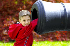 Young Boy WIth Hand In Cannon. Young Boy Sticking His Hand in The Barrel of a Cannon Royalty Free Stock Photos