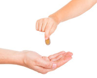 Young boy hand giving a charity. Young boy hand giving a coin to a male hand as a charity Stock Image