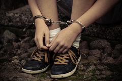 Young boy in handcuffs and sneakers. Sitting with his hands resting on his shoes on old cobblestones after being arrested, close up view of the manacles Royalty Free Stock Image