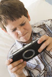 Young boy with handheld game indoors. Looking unhappy Royalty Free Stock Photography