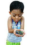 Young boy with hands of marbles. Young asian boy with hands of marbles royalty free stock images