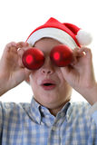 Young boy hanging ornaments on a Christmas tree. Young boy hanging ornaments, funny stock photo