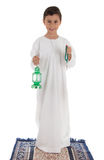 Young boy happily catching Ramadan lantern and rosary. Standing on praying carpet Stock Image