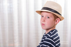 Young boy with hat looking angry into the camera Royalty Free Stock Images