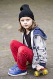 Young boy with hat sitting on skateboard Stock Photos