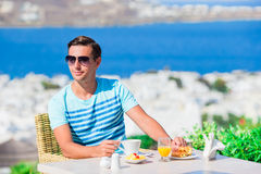 Young boy having breakfast at outdoor cafe with amazing view on Mykonos town. Man drinking hot coffee on luxury hotel Stock Photo