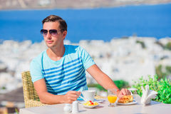 Young boy having breakfast at outdoor cafe with amazing view on Mykonos town. Man drinking hot coffee on luxury hotel. Man having breakfast at outdoor cafe with stock images