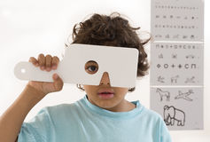 Young boy is having eye exam. Young boy s having eye exam performed by optician, optometrist or eye doctor Royalty Free Stock Photo