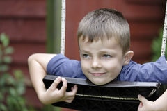 Young boy having fun outside on a swing Royalty Free Stock Images