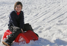 Young boy having fun on the red sleigh in the mountains in winte Stock Images
