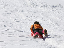 Young boy having fun on the red sleigh in the mountains Stock Photo