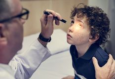 Young boy having his eyes checked. By the doctor stock images