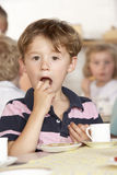 Young Boy Having Tea at Montessori/Pre-School. Enjoying his Food stock photos
