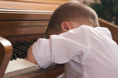 Young Boy with Head on the Piano Royalty Free Stock Photography