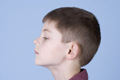 Young Boy Head Shot Side Profile. Young boy head shot from the side profile not smiling on a blue background Royalty Free Stock Images