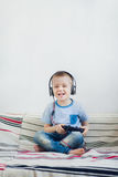 Young boy in headphone playing with playstation at home. Smiling young boy in headphone playing video games at home Stock Image