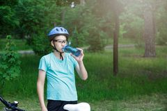 Young boy in helmet and green t shirt cyclist drinks water from bottle in the park. Smiling cute Boy on bicycle in the forest royalty free stock photos