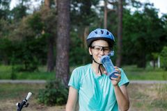 Young boy in helmet and green t shirt cyclist drinks water from bottle in the park. Smiling cute Boy on bicycle in the forest stock image