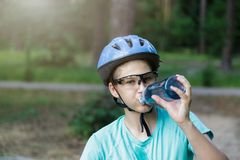 Young boy in helmet and green t shirt cyclist drinks water from bottle in the park. Smiling cute Boy on bicycle in the forest stock photos