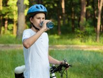 Young boy in helmet and white t shirt cyclist drinks water from bottle in the park. Smiling cute Boy on bicycle in the forest stock photo