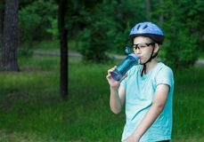 Young boy in helmet and green t shirt cyclist drinks water from bottle in the park. Smiling cute Boy on bicycle in the forest royalty free stock image