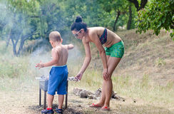 Young boy helping at the barbecue Stock Photo