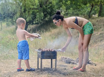 Young boy helping at the barbecue Royalty Free Stock Image