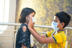 Free Young Boy Helping His Sister To Adjust Her Protective Mask On Face. Kids In Isolation, Quarantine, Stay At Home, Due To Covid-19 Royalty Free Stock Photo - 178180555
