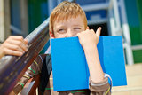 Young boy is hiding behind book. Young secretive boy with book in front of school Royalty Free Stock Photography