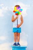 Young boy hiding face behind the windmill Stock Photos