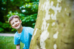 Young boy hiding at tree Royalty Free Stock Photos