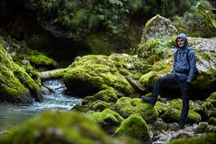 Hiker boy by the river. Young boy hiker with backpack near a river with mossy boulders Royalty Free Stock Images