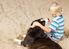 Young boy with his arm around his dog. Young boy sitting with arm around his pet dog at the beach Royalty Free Stock Images