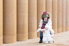 Young boy and his baby sister on a walk next to a modern building entrance with pillars Royalty Free Stock Images