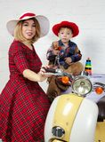 Mother and child wearing old fashioned clothes posing near scoot Stock Photo